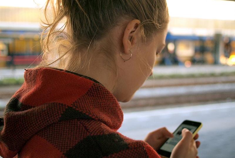 eine Frau, die Smartphone hält, während sie draußen steht
