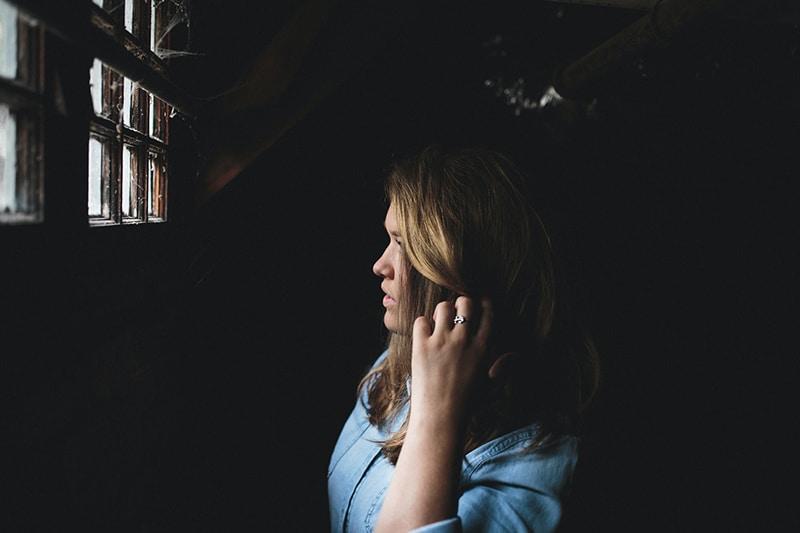 Eine Frau, umgeben von einem Spinnennetz, das unter einem Fenster steht