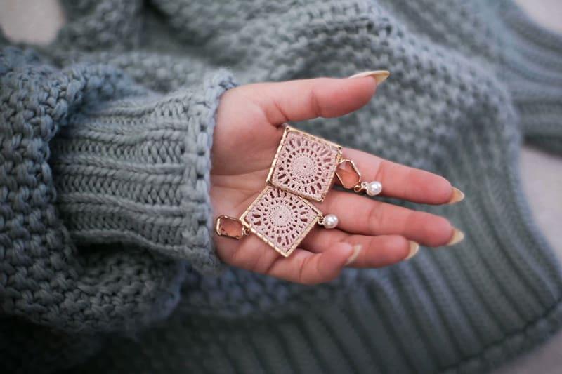 eine Frau, die ein Paar Ohrringe in der Hand hält