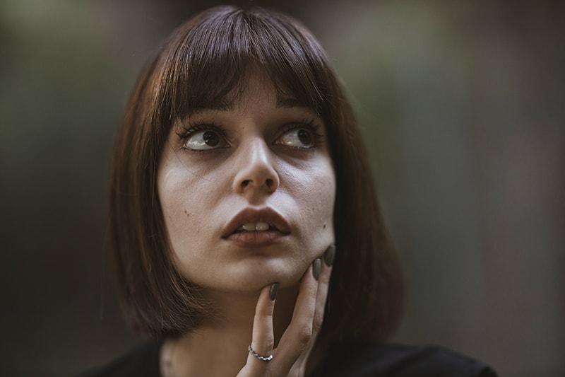 eine Frau mit einem müden Gesichtsausdruck, der das Kinn mit der Hand berührt