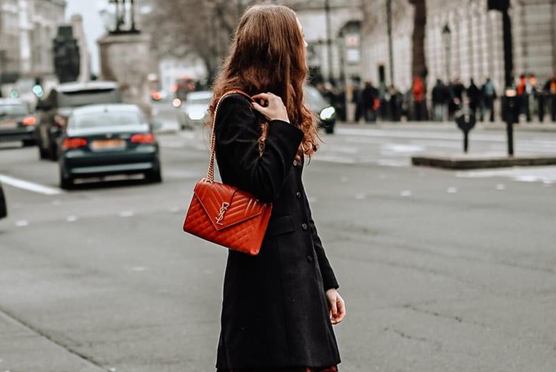 Eine Frau mit roter Handtasche steht auf der Straße und wartet auf einen Mann