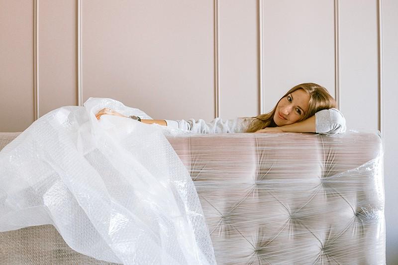 eine Frau, die mit einem Lächeln im Gesicht ein neues Kopfteil fürs Bett auspackt