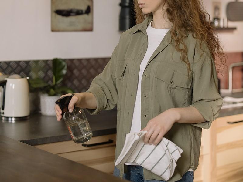 eine Frau, die eine Küche putzt, die Tuch und Spray hält