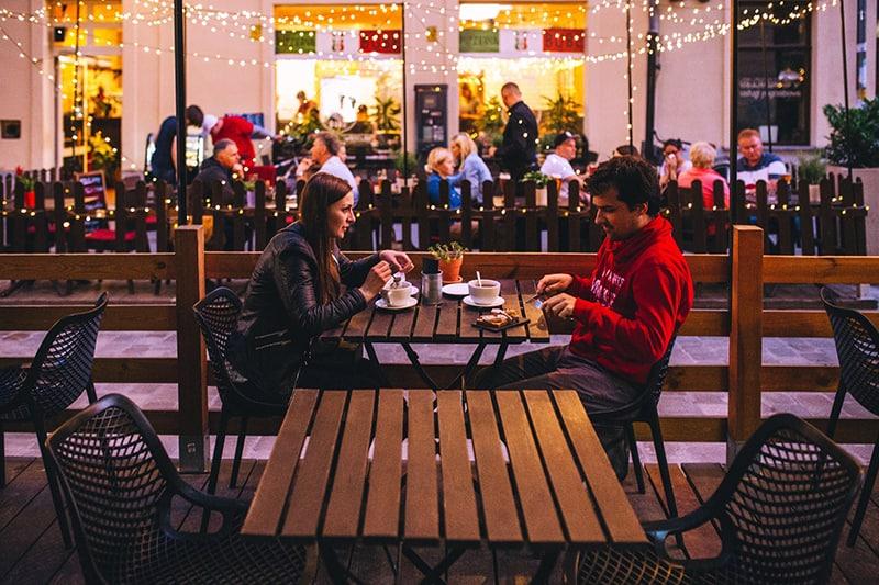 eine Frau und ein Mann, die auswärts essen umgeben von Lichtern