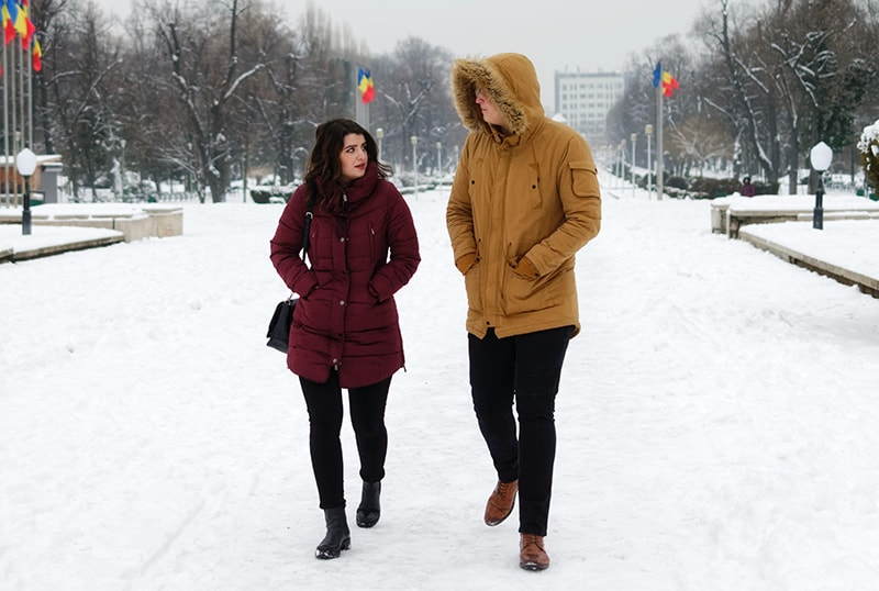 eine Frau und ein Mann reden beim spazierengehen auf dem schnee