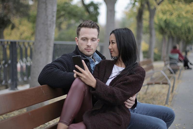 eine Frau und ein Mann sitzen zusammen auf der Bank, während eine Frau ein Smartphone benutzt