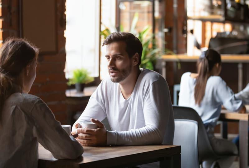 Eine Frau und ein Mann unterhalten sich in Speed-Dating, während sie am Tisch sitzen