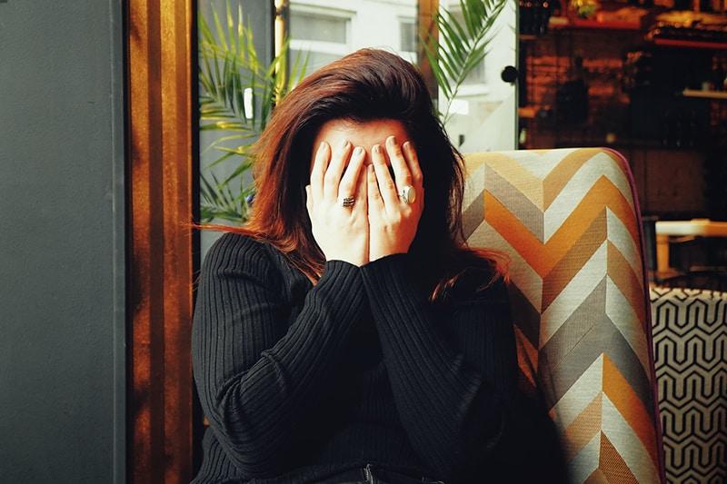 eine Frau, die ihr Gesicht mit Handflächen versteckt