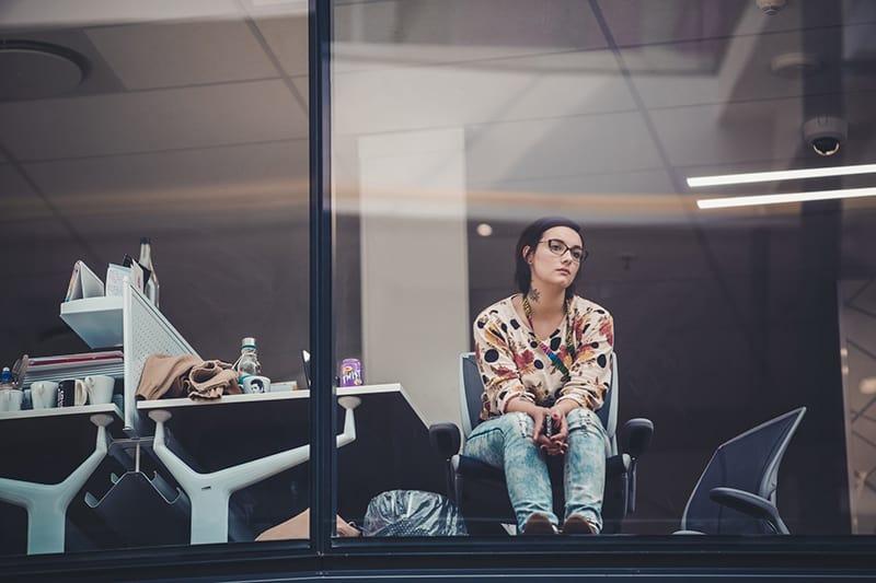eine Frau, die auf Antwort wartet, während sie im Büro sitzt