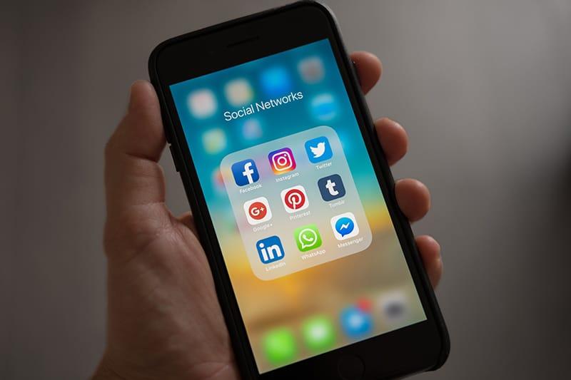 eine Person, die ein Smartphone in der Hand hält und Social-Media-Apps anzeigt