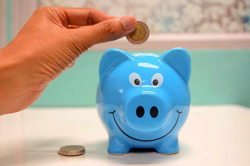 eine Person, die die Münze über dem Sparschwein hält