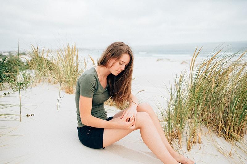 eine einsame Frau, die tagsüber an der Küste sitzt