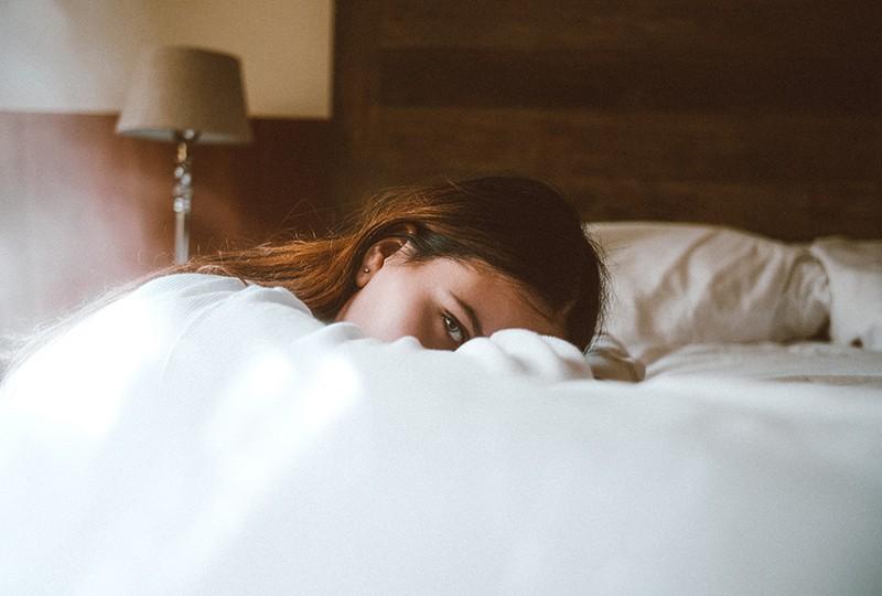 eine einsame Frau, die sich mit dem Kopf auf das Bett stützt