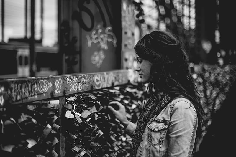 eine einsame Frau, die vor der Wand des Vorhängeschlosses steht und sie berührt