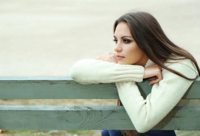 eine einsame Frau sitzt auf einer Bank