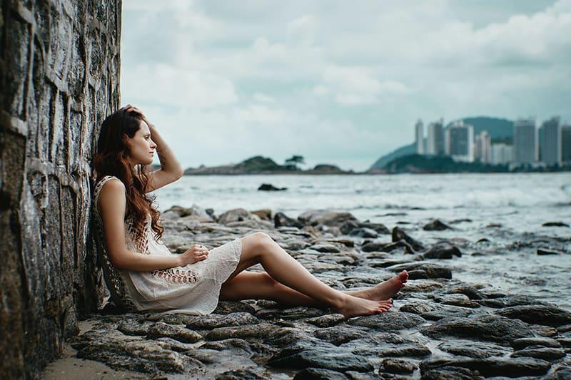 eine enttäuschte Frau, die alleine auf dem Boden in der Nähe eines Gewässers sitzt