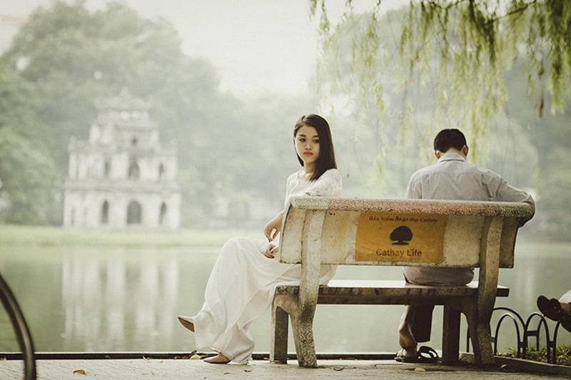Eine enttäuschte Frau sitzt auf der Bank neben einem Mann in der Nähe des Sees