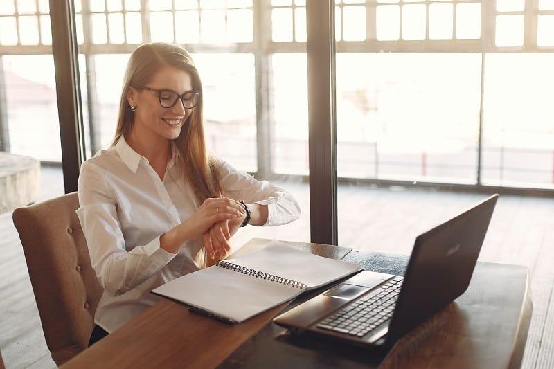 eine lächelnde Frau, die auf einer Uhr auf die Uhr schaut, um das Büro zu verlassen