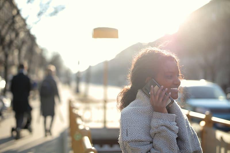eine lächelnde Frau, die einen Anruf hat, während sie auf der Straße steht
