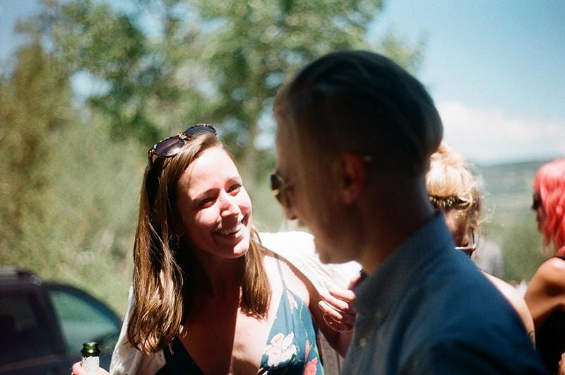 eine lächelnde Frau, die mit einem Mann spricht, während sie draußen steht