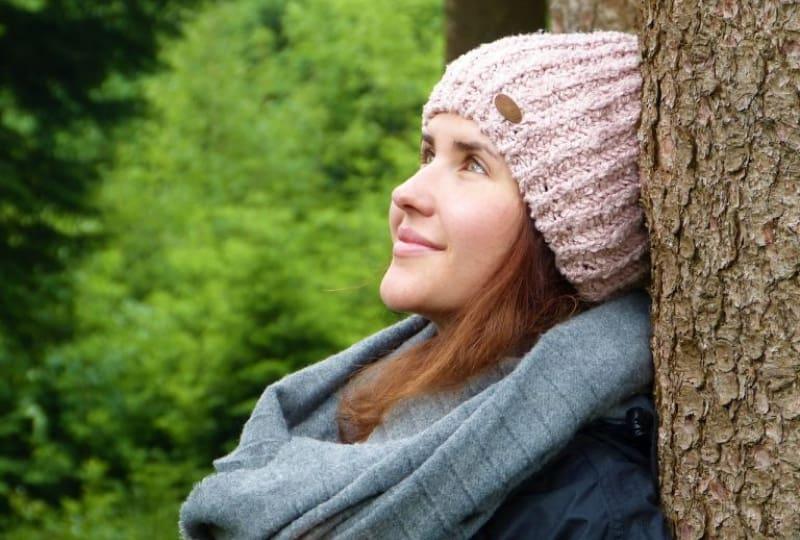 eine-lächelnde-Frau-im-Wald-die-zum-Himmel-aufblickt