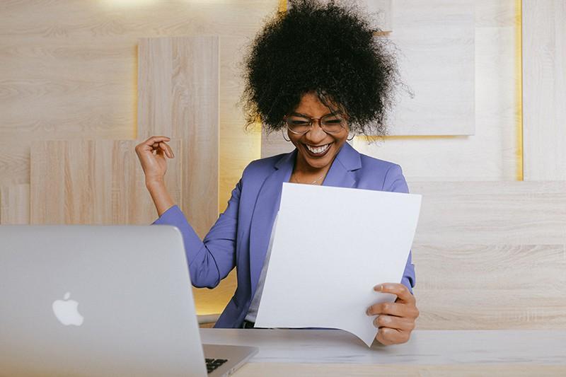 eine lachende Frau, die im Büro einen Brief liest