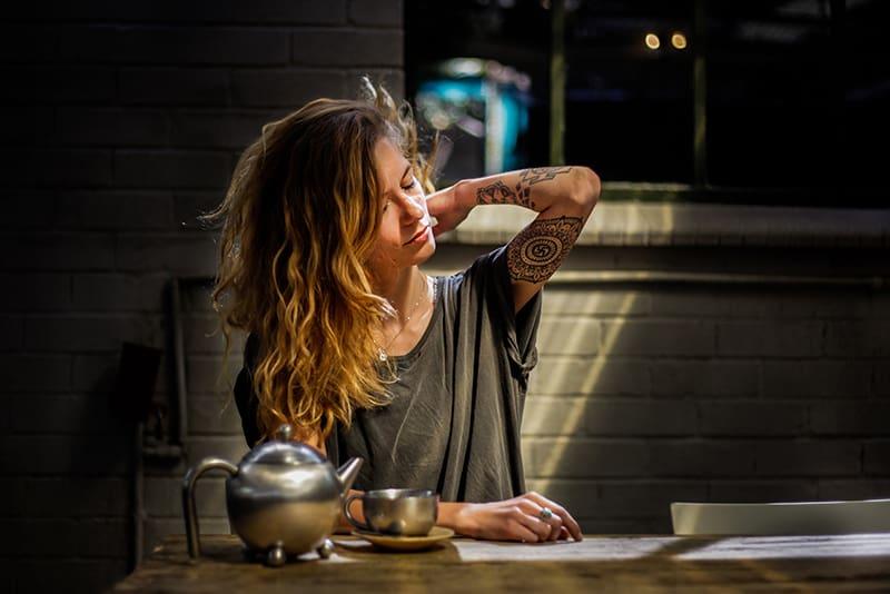 eine müde Frau, die alleine am Tisch sitzt und Tee trinkt