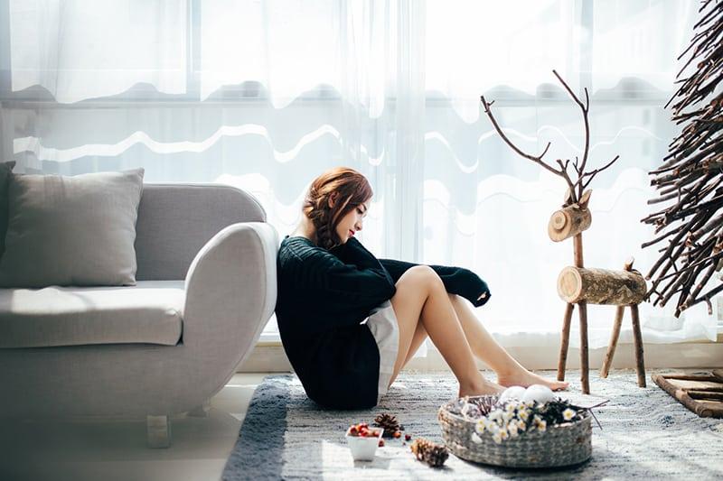 eine nachdenkliche Frau, die auf dem Boden sitzt und sich auf das Sofa lehnt
