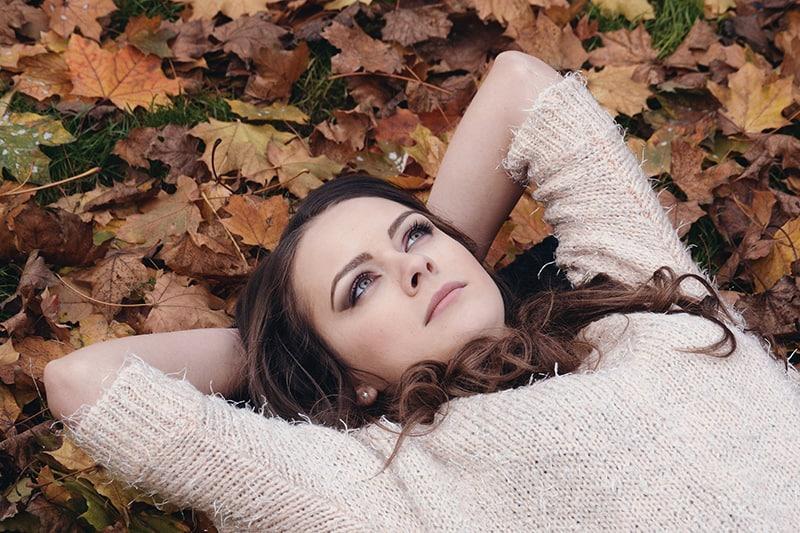 eine nachdenkliche Frau, die tagsüber auf den Blättern liegt