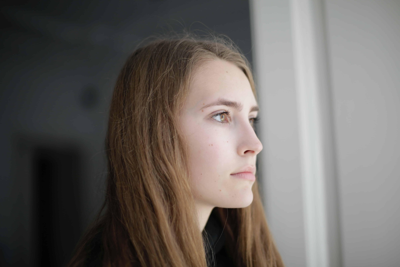 eine nachdenkliche Frau, die in einem Wohnzimmer neben dem Fenster steht