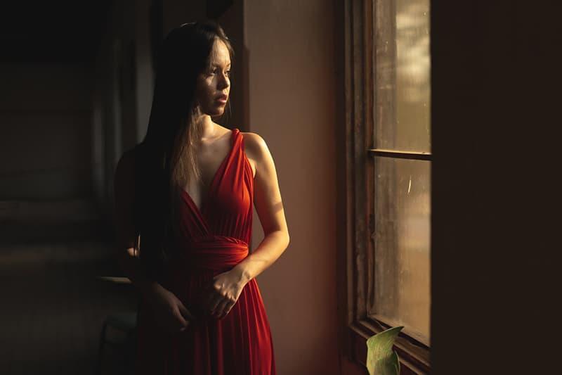 eine nachdenkliche Frau, die allein am Fenster stand