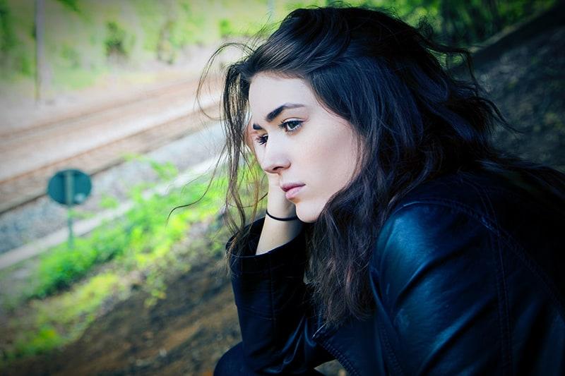 eine nachdenkliche Frau, die beiseite schaut, während sie in der Nähe der Eisenbahn sitzt