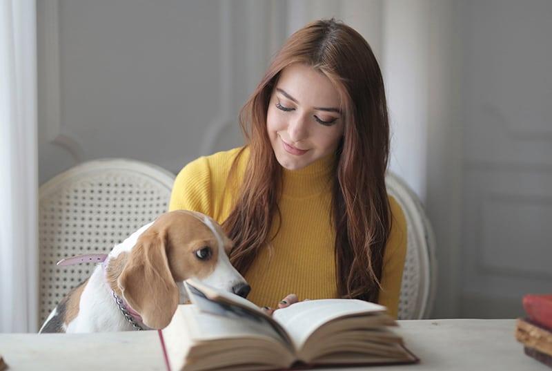 eine positive Frau, die den Hund ansieht, während sie mit Buch vor ihr sitzt