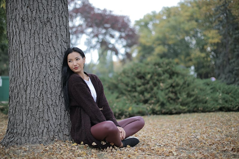 eine positive junge Dame, die auf dem Boden sitzt und sich auf den Baum stützt