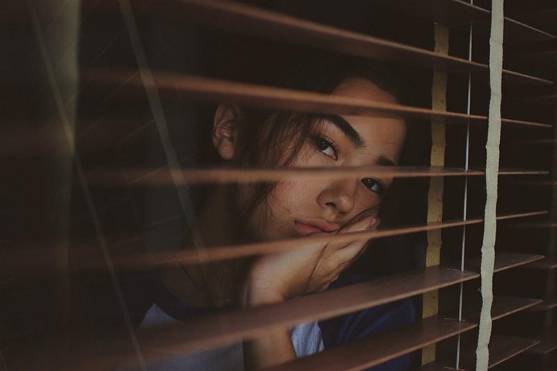 eine traurige Frau, die durch das Fenster schaut und an ihren Ex-Freund denkt