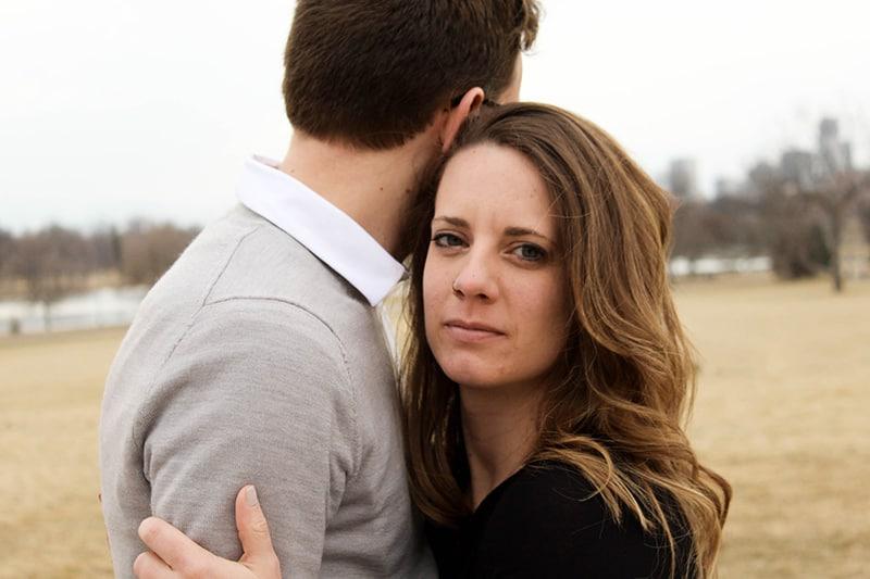 eine traurige Frau, die einen Mann umarmt, während sie draußen steht