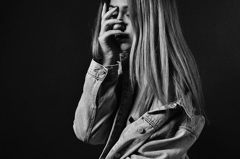 eine traurige Frau, die ihr Gesicht mit der Hand berührt, während sie allein steht