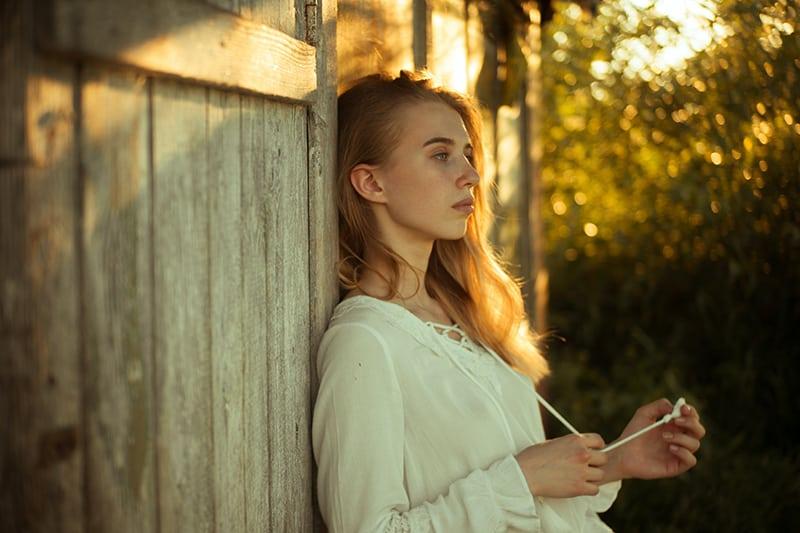 eine traurige Frau, die sich gegen eine Holzwand lehnt und in die Ferne schaut