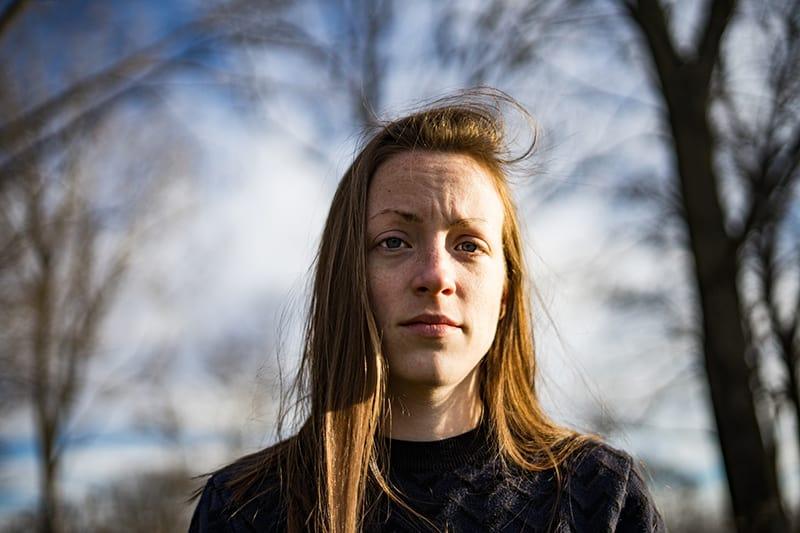 eine traurige Frau mit langen blonden Haaren, die im Wald steht