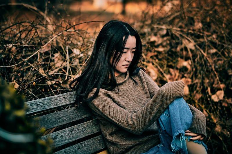 eine traurige Frau, die auf der Bank im Wald sitzt