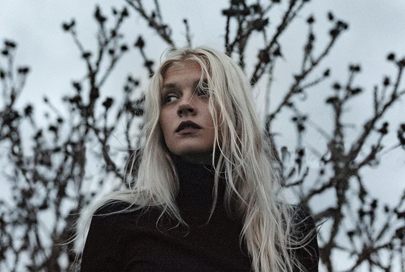 eine verwirrte Frau, die allein draußen steht und von Bäumen umgeben ist