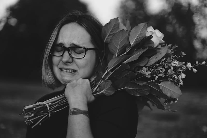 eine weinende Frau, die mit Blumen in der Hand steht