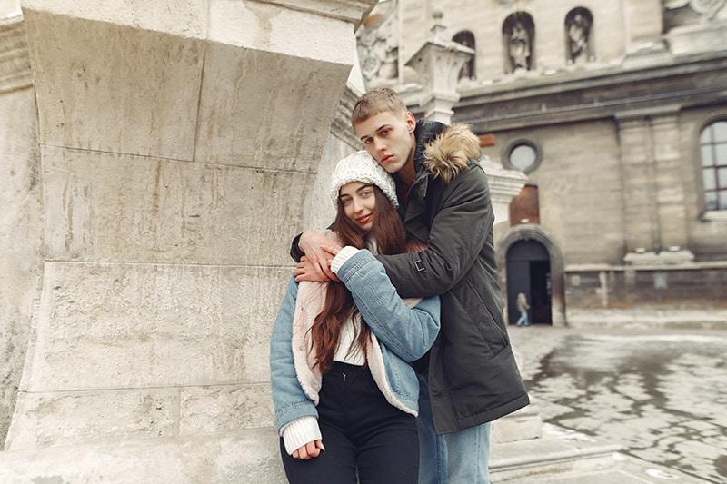 ernsthafter Mann, der eine lächelnde Frau umarmt, während er in der Nähe von Gebäuden steht