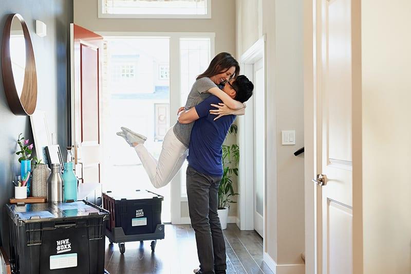 Der Mann hebt die Frau nach der Begegnung im Haus hoch