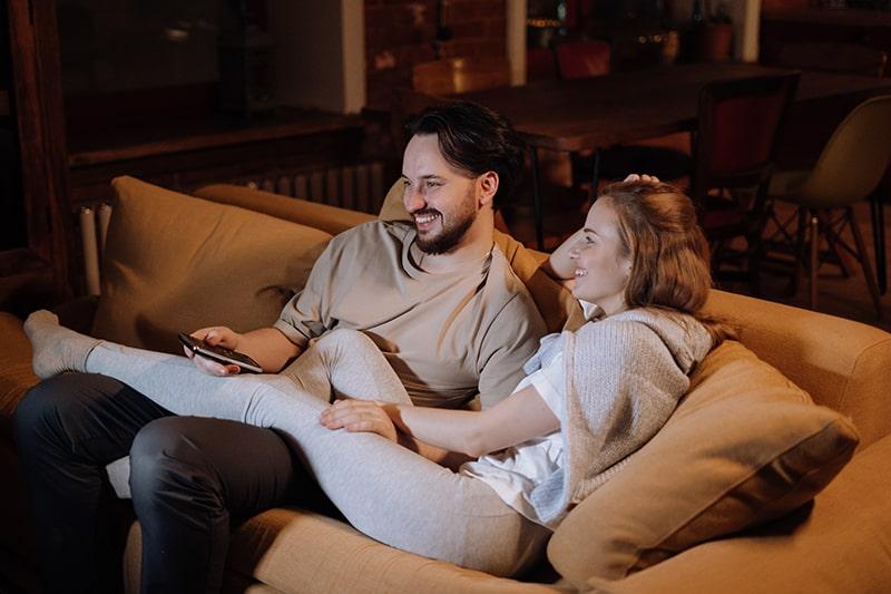 lächelndes Liebespaar, das abends auf der Couch sitzt