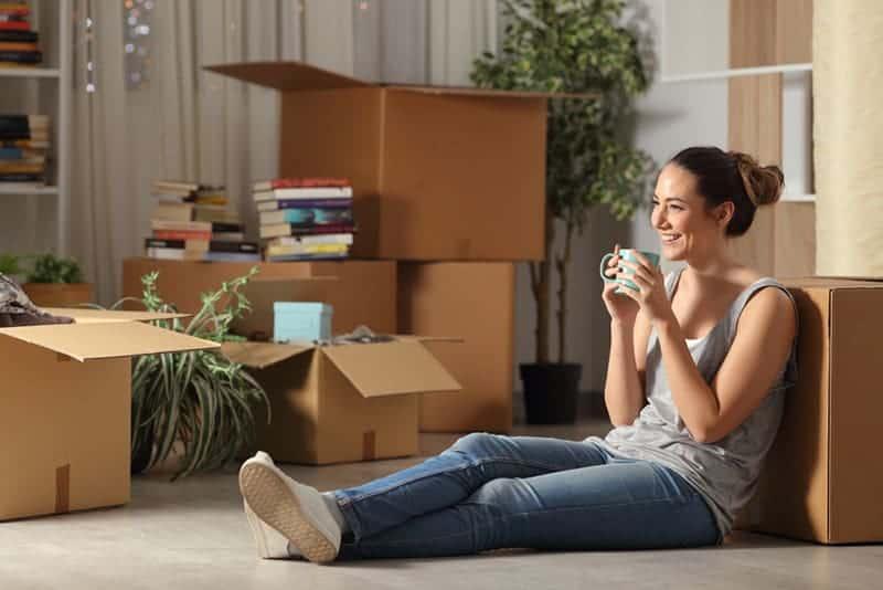 lächelnde Frau, die zu Hause auf dem Boden sitzt