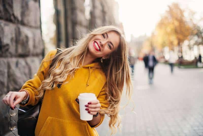 lächelnde Frau im orange Sweatshirt draußen hält eine Tasse