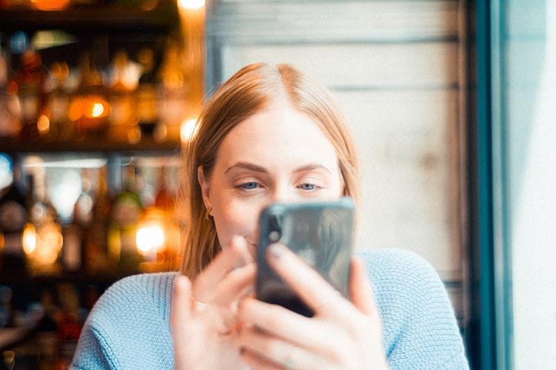lächelnde Frau mit einem Smartphone neben Fenster