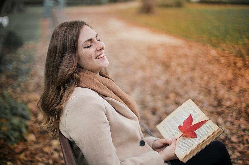 lachende Frau, die ein Buch hält, während sie alleine auf der Bank sitzt