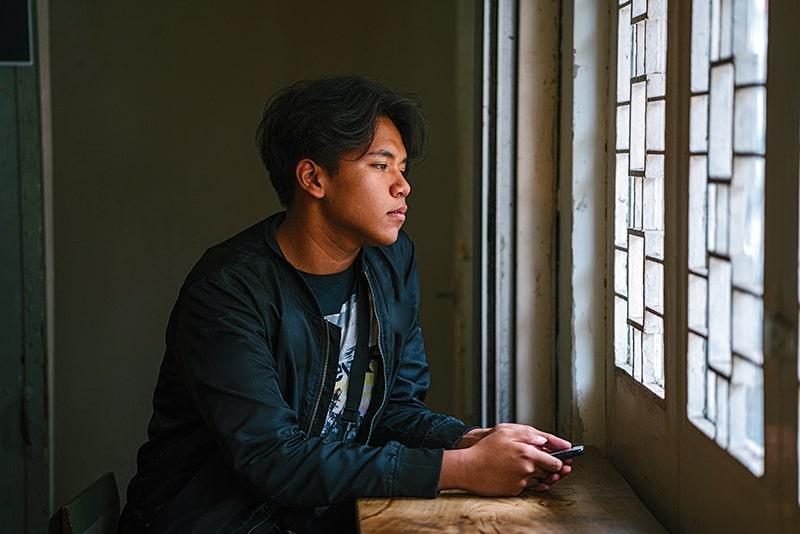 trauriger Mann, der Smartphone neben Fenster hält